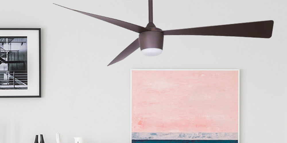 A room with a ceiling fan and art