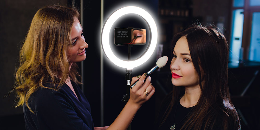 A person doing another person's makeup, with the aid of a phone tripod with a ring light