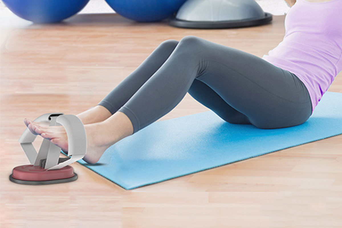 A person doing sit ups with a device to assist
