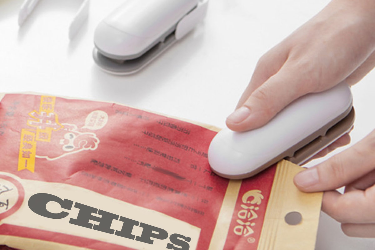 A person sealing a bag of chips with a mini sealing machine