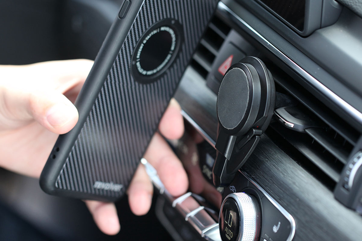 A person putting their phone onto a car phone mount