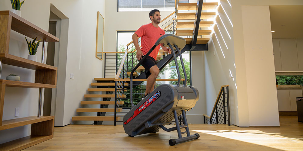 A man runs on an elevated treadmill on an incline in his home