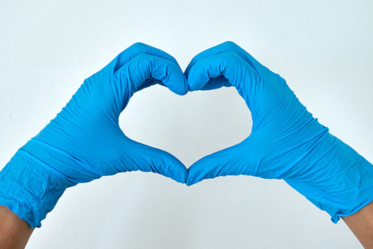 A person wearing blue gloves, with their hands in the shape of a heart