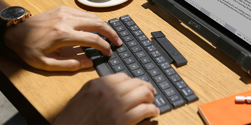 A person typing on a wireless keyboard