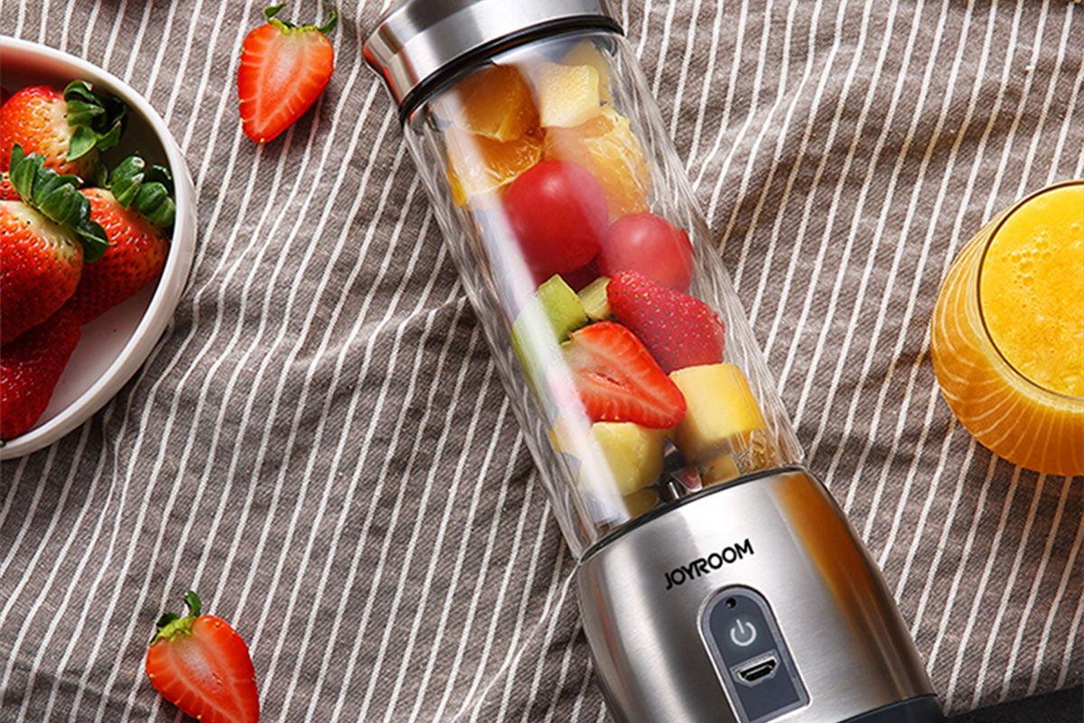 A mini blender filled with fruit.