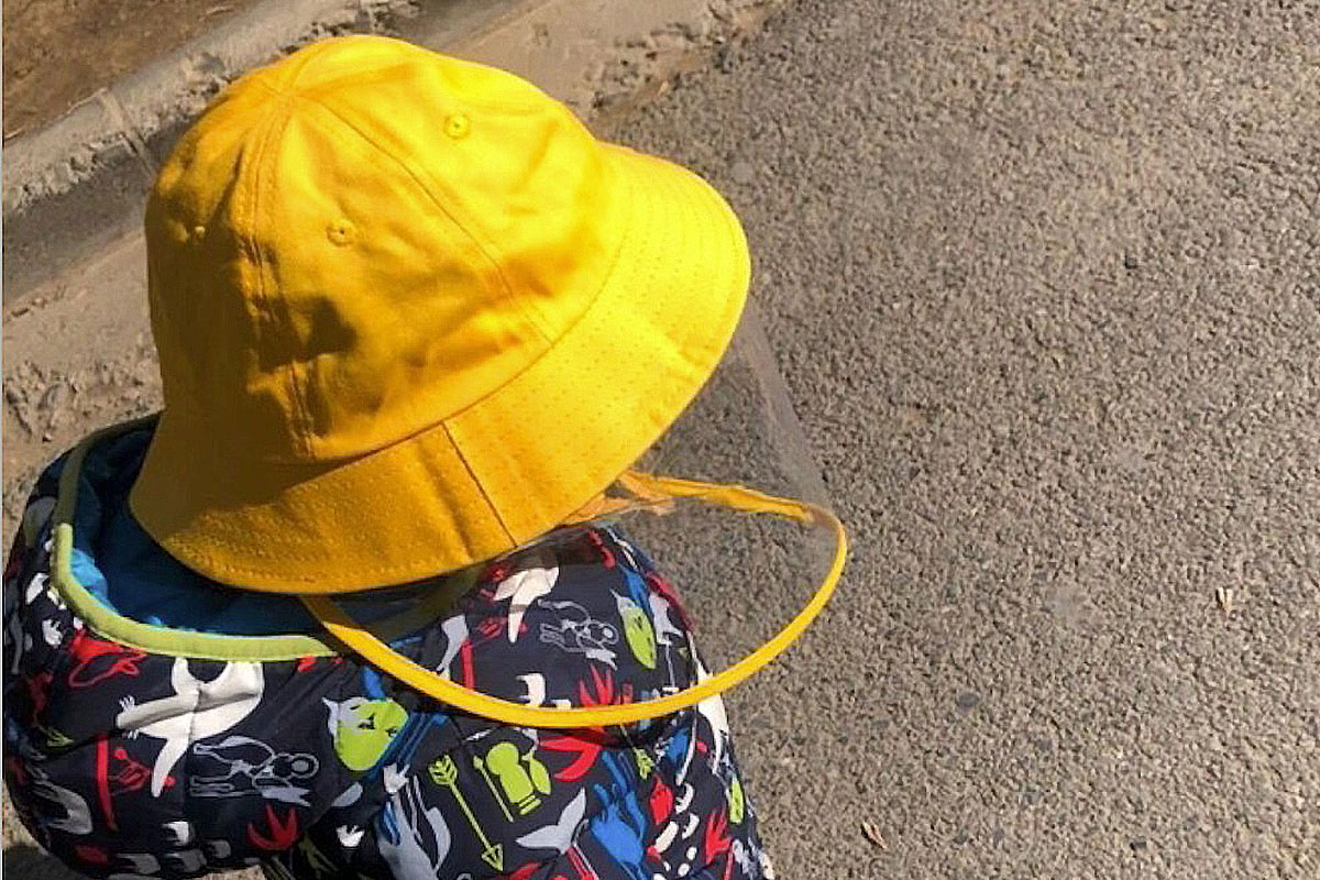 A child wearing a bucket hat with a face shield attached