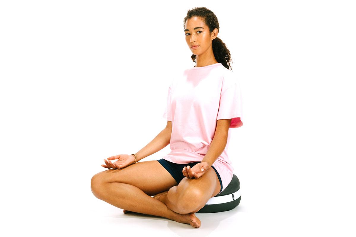 A person meditating on a cushion
