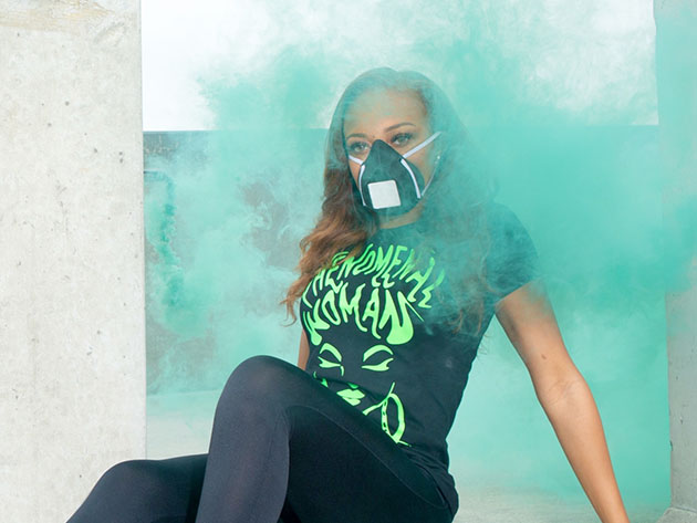 A person wearing a face mask surrounded by turquoise smoke