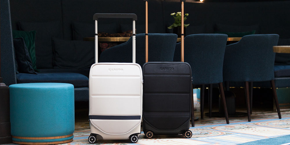 Two pieces of rolling luggage in a dark room