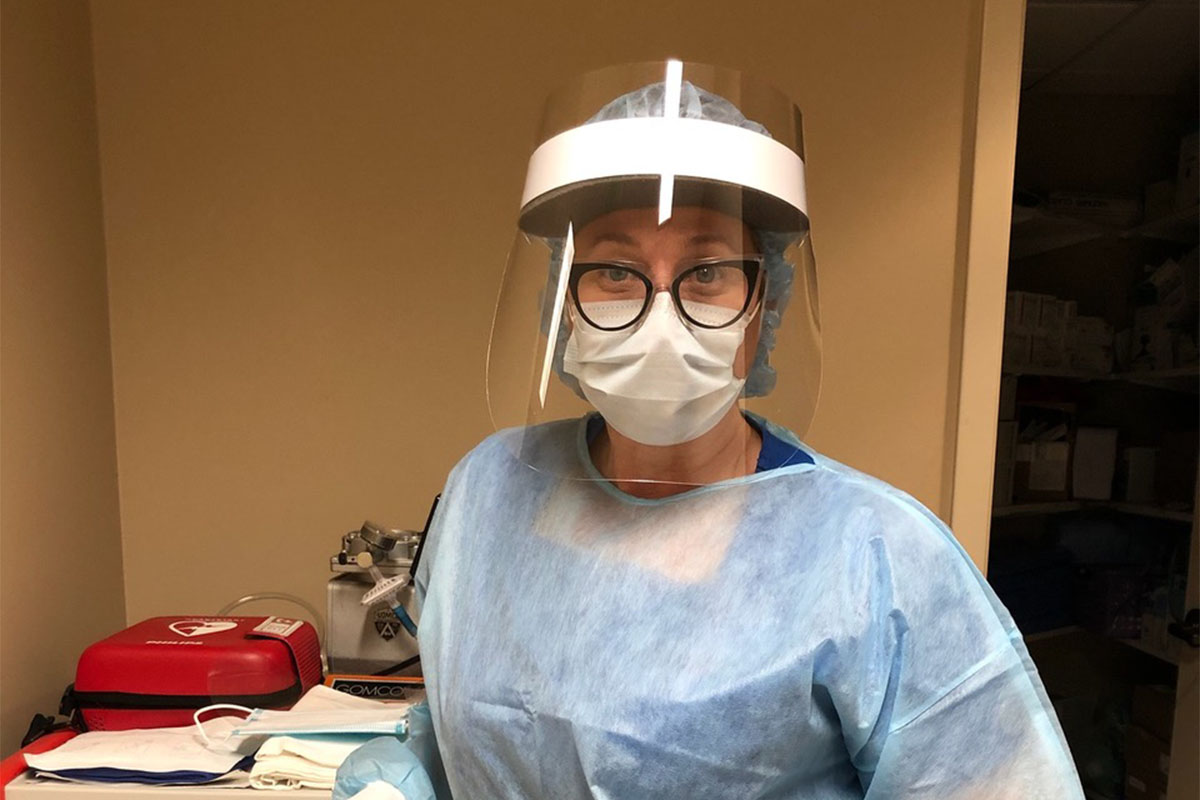 A person wearing assorted Personal Protective Equipment, including a face shield.