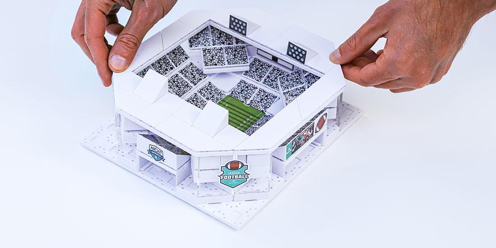 Hands building a stadium model