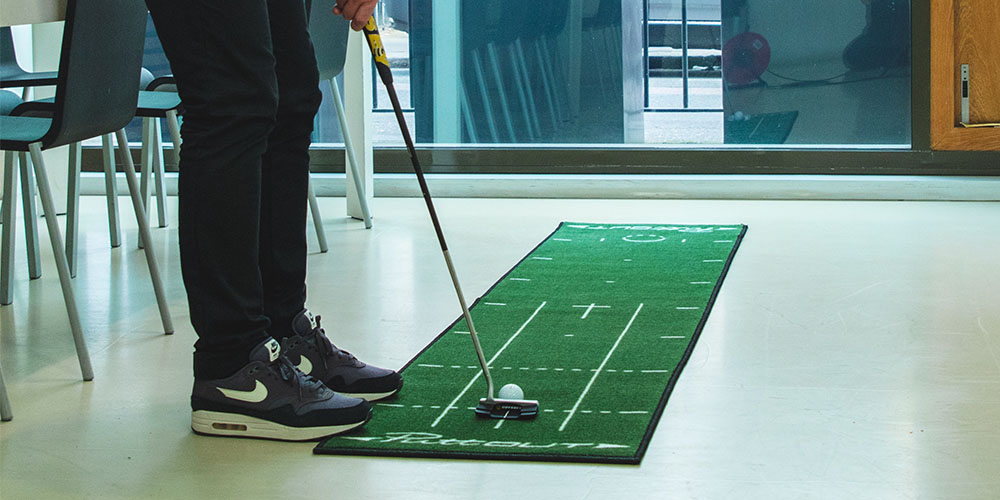 A golf club hitting a ball on a strip of indoor green
