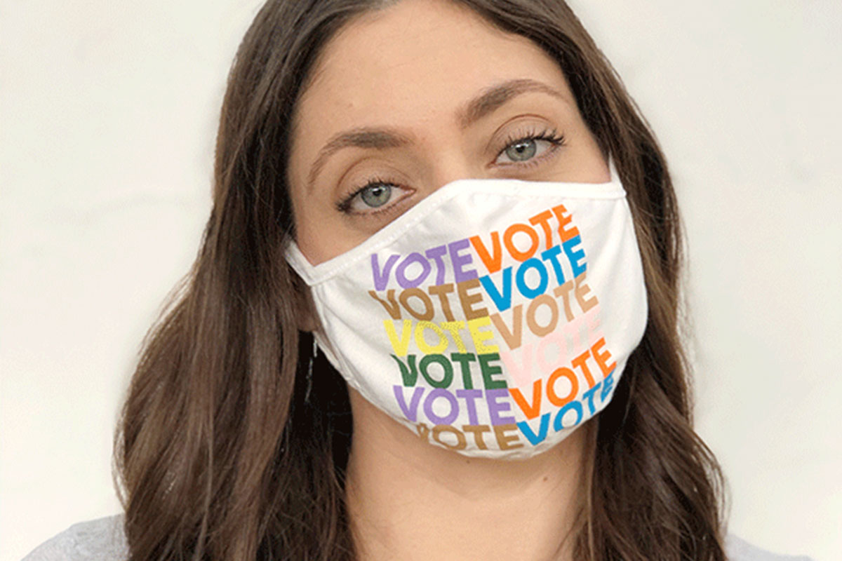 """A person wearing a face mask that repeats the word """"VOTE"""" on it."""